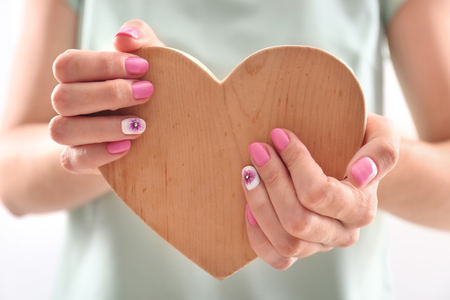 Woman with stylish color nails holding wooden heart, closeup Stock Photo