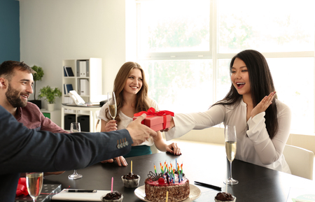 Young man giving birthday present to his colleague at party in office
