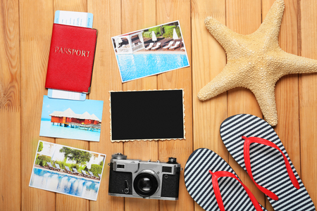 Composition with flip-flops, passport, cards, starfish and photo camera on wooden background. Travel planning concept Imagens