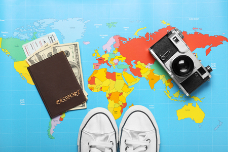 Composition with photo camera, gumshoes and passport on world map. Travel planning concept Imagens