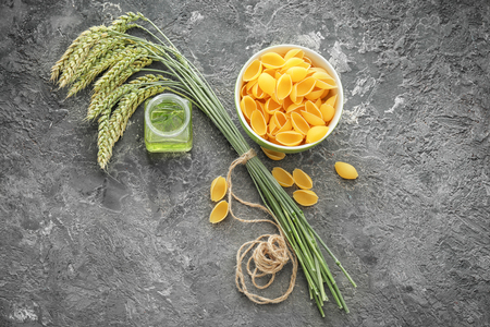 Wheat spikelets with pasta and oil on grey background
