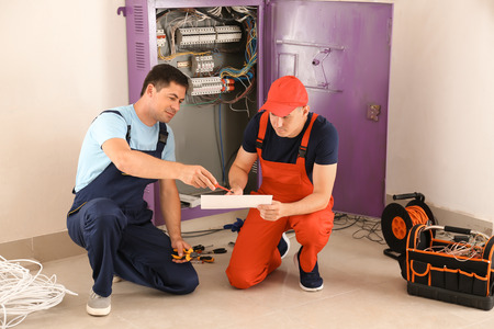Two electricians with house plan near distribution board indoors Stock Photo