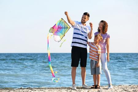 Happy family flying kite near sea