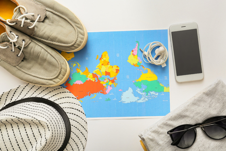Composition with world map, mobile phone, clothes and accessories on white background. Travel planning Фото со стока
