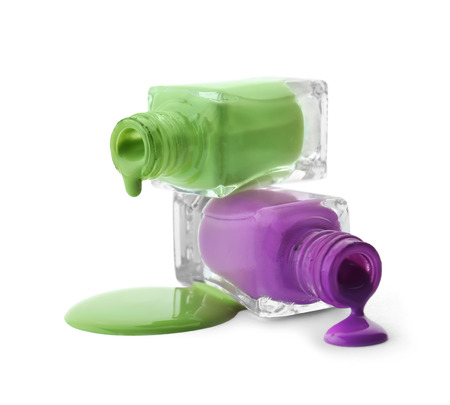 Open bottles with dripping nail polishes on white background