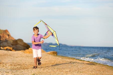 Little boy flying kite near sea