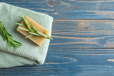 Handmade soap with rosemary and towel on wooden table
