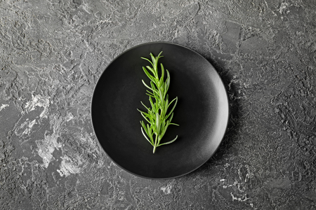 Plate with fresh rosemary on grey textured background Imagens