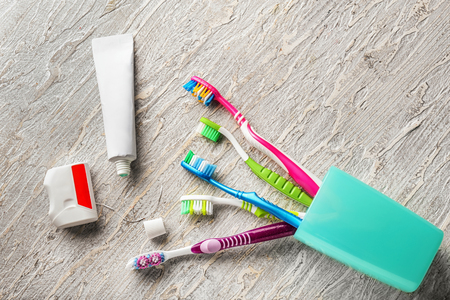 Toothbrushes, dental floss and paste on wooden background