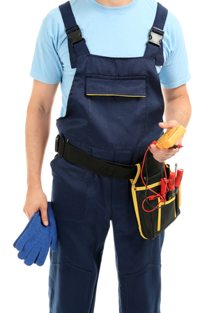 Electrician with multimeter and tools on white background Foto de archivo
