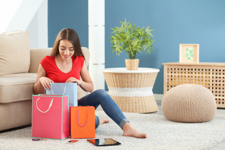 Young woman looking into shopping bag at home
