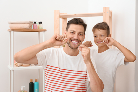 Little boy and his father flossing teeth in bathroom