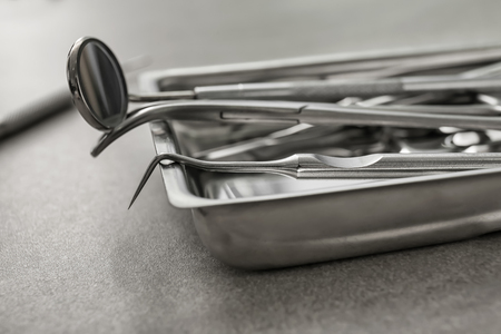 Tray with dentist's tools on grey table