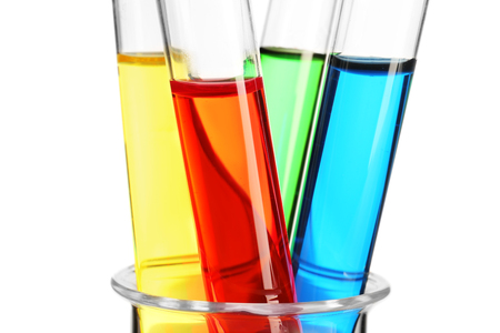 Test tubes with colorful liquids in glass beaker on white background, closeup