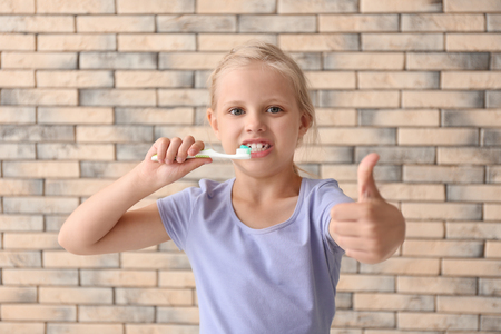 Little girl with toothbrush showing thumb-up gesture against brick wall