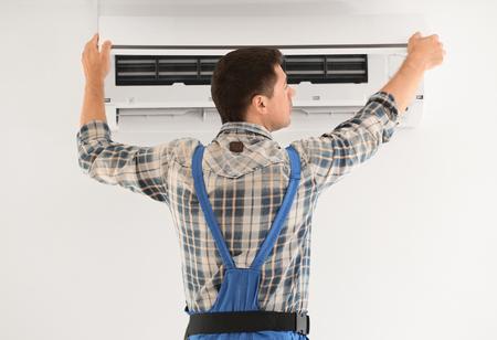 Electrician repairing air conditioner indoors Reklamní fotografie