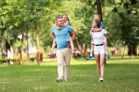 Happy family walking together in green park Stockfoto