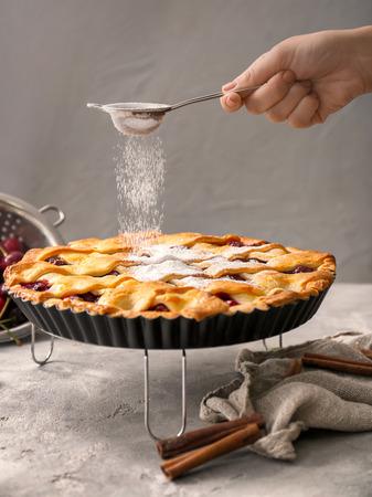 Woman sprinkling sugar powder over sweet homemade cherry pie in kitchen