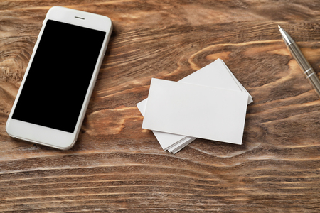 Blank business cards with mobile phone and pen on wooden table