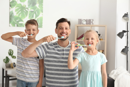 Man and his little children brushing teeth at home 스톡 콘텐츠