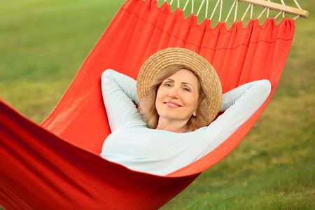 Mature woman resting in hammock outdoors