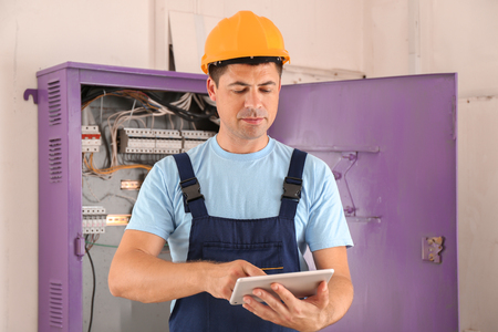Electrician with tablet PC near distribution board indoors