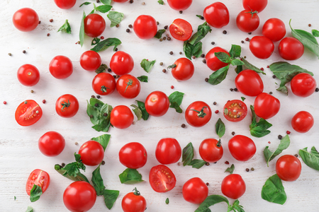 Fresh cherry tomatoes with basil on light background