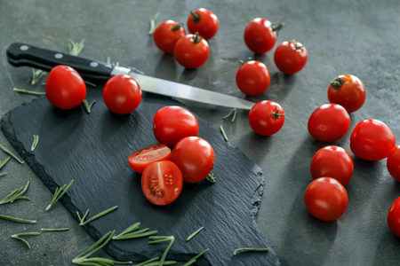 Fresh cherry tomatoes with slate plate and knife on grey background