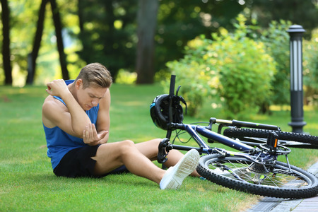 Young man fallen off his bicycle in park