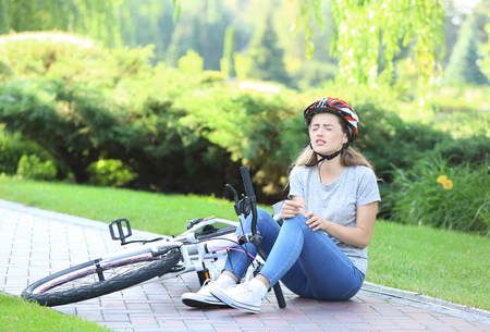 Young woman fallen off her bicycle in park
