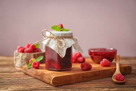 Composition with sweet homemade raspberry jam on wooden table
