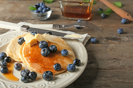 Plate with delicious pancakes and berries on wooden table Standard-Bild - 114599122