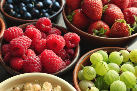 Bowls with various ripe berries on table, closeup Archivio Fotografico