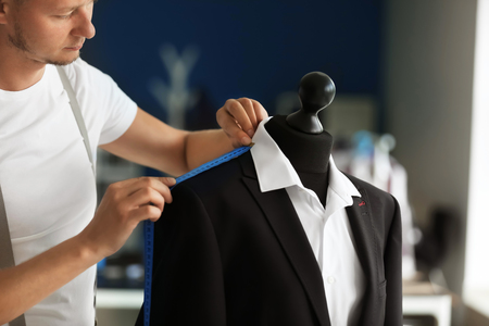 Young tailor taking measurements of male jacket on mannequin in atelier