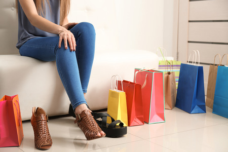 Young woman choosing shoes while sitting on sofa in shop