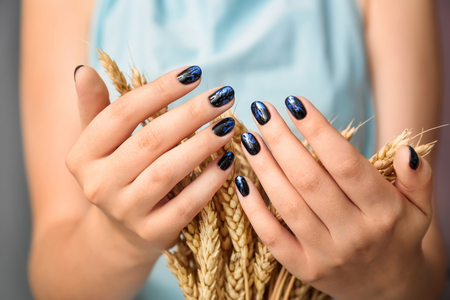 Woman with stylish color nails holding wheat ears, closeup