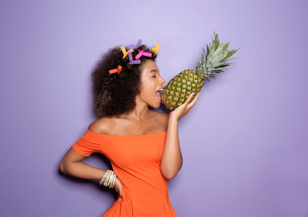 Beautiful African-American woman with pineapple on color background 스톡 콘텐츠