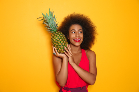 Beautiful African-American woman with pineapple on color background Stock Photo