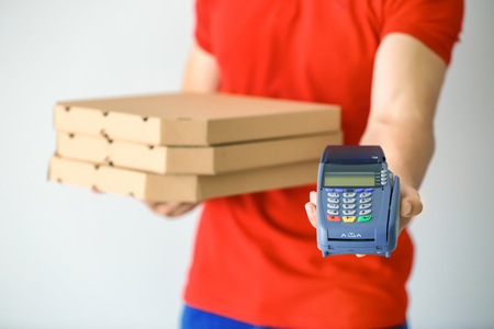 Young man with pizza boxes and bank terminal on light background. Food delivery service