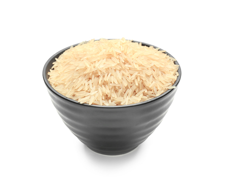 Bowl with parboiled rice on white background