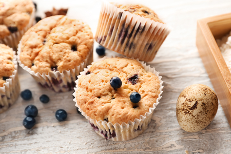 Tasty blueberry muffins on light textured background