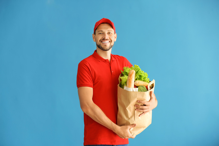 Man holding paper bag with fresh products on color background. Food delivery service
