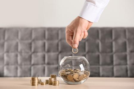 Hombre poniendo monedas en un frasco de vidrio sobre la mesa. Concepto de ahorro Foto de archivo