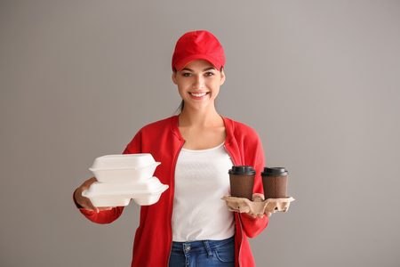 Young woman with plastic containers and cups of coffee on grey background. Food delivery service
