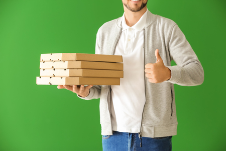 Man with pizza boxes showing thumb-up gesture on color background. Food delivery service