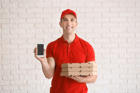 Young man with pizza boxes and mobile phone near white brick wall. Food delivery service Imagens