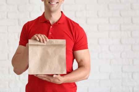 Young man with paper bag near white brick wall. Food delivery service