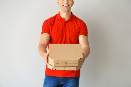 Young man with pizza boxes on light background. Food delivery service Imagens - 114665133
