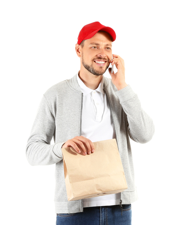 Man with paper bag talking by mobile phone on white background. Food delivery service Imagens