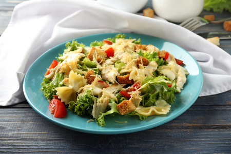 Tasty Caesar salad with pasta on plate